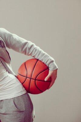 Sportlich jugendlich Mädchen hält Basketball mit einer Hand.
