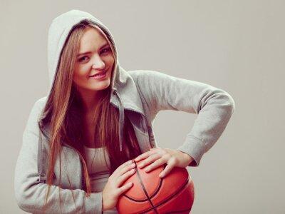 Sportlich jugendlich Mädchen in der Haube hält Basketball.