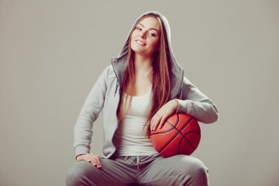 Sportlich jugendlich Mädchen in der Kapuze, die Basketball anhält.
