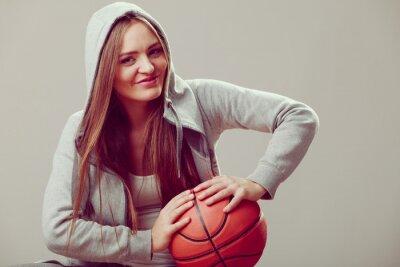 Sportlich Teenager-Mädchen in der Haube hält Basketball.