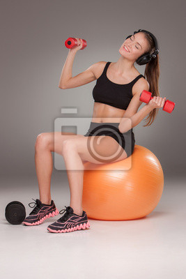 Sportliche Frau macht Aerobic-Übung mit Hanteln
