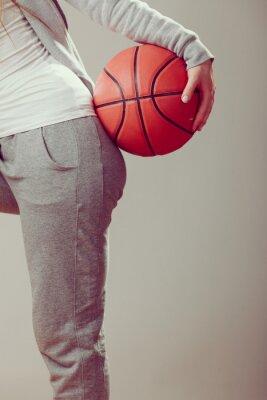 Sportliche jugendlich Mädchenholding-Basketball mit einer Hand.
