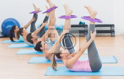 Sportliche Leute mit dem Trainieren schellt im Eignungsstudio