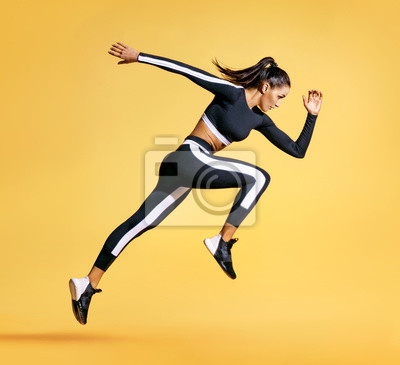 Bild Sporty woman runner in silhouette on yellow background. Photo of attractive woman in fashionable sportswear. Dynamic movement. Side view. Sport and healthy lifestyle