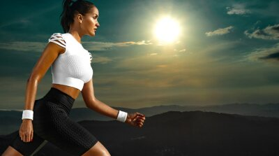 Sporty young woman and fit athlete runner running on the sky background in the mountains. The concept of a healthy lifestyle and sport. Woman in black and white sportswear.