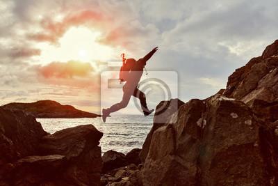 Bild Springender Mannwanderer über einer Lücke zwischen zwei Felsen