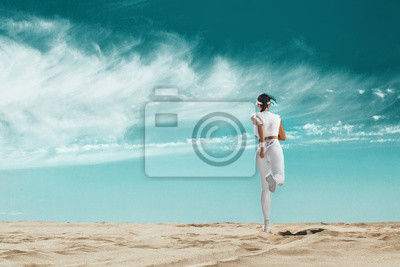 Sprinter, athlete runner. Sporty young and fit woman running on the sky background. The concept of a healthy lifestyle and sport. Woman in white sportswear.