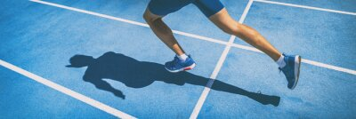 Bild Sprinting man runner sprinter athlete running shoes and legs on track and field lane run race competing fast panoramic banner background.