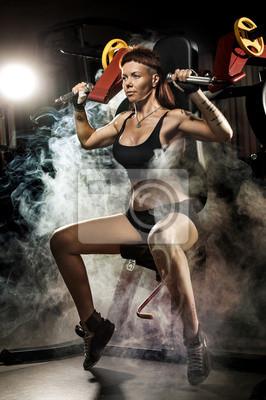 Starke Frau in der Turnhalle tun Übungen auf einer Maschine