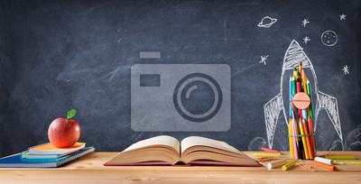Bild Start Schulkonzept - Zubehör auf Schreibtisch und Rocket auf Tafel gezeichnet