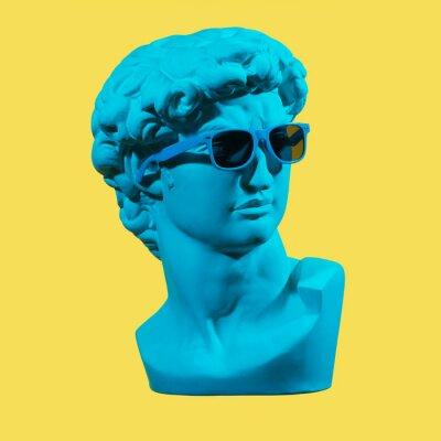 Bild Statue. Earphone. Isolated. Gypsum statue of David's head. Man. Creative. Plaster statue of David's head in blue sunglasses. Minimal concept art.