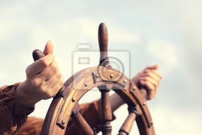 Bild Steering hand wheel ship on sky background, hand hold hand wheel