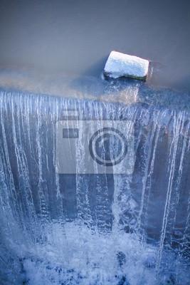 Stein bedeckt mit Schnee am Rande eines Wasserfalls