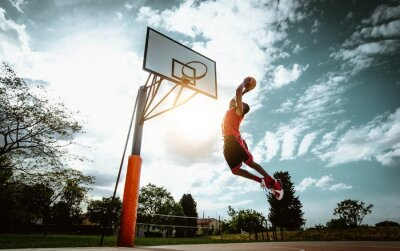 Bild Street basketball player making a powerful slam dunk on the court - Athletic male training outdoor at sunset - Sport and competition concept