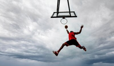 Bild Street basketball player making a powerful slam dunk on the court - Athletic male training outdoor on a cloudy sky background - Sport and competition concept