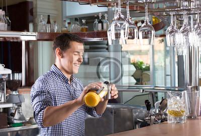 Bild Strömendes Getränk des glücklichen lächelnden Barmixers in ein Stahljigger.