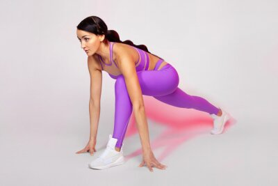 Strong athletic woman, doing exercise on white background wearing sportswear. Fitness and sport motivation.
