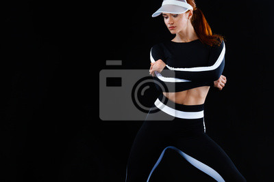 Strong athletic woman , posing on black background wearing in sportswear. Energy fitness and sport motivation. Copy space.