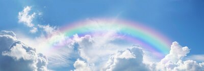 Bild Stunning blue sky panoramic rainbow - big fluffy clouds with a giant arcing rainbow against a  beautiful summer time blue sky with copy space for messages