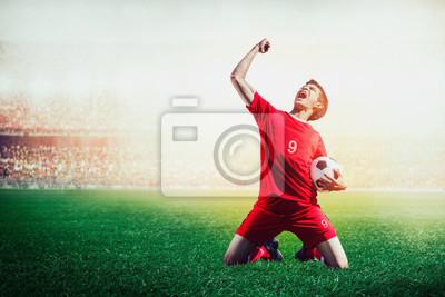 Stürmerfußballfußballspieler im roten Teamkonzept, das Ziel im Stadion während des Spiels feiert