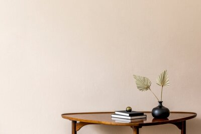 Bild Stylish composition on the design wooden table with books and paper flowers in vase. Beige background walls. Minimalistic conept of living room. Copy space. Template.