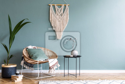 Bild Stylish minimalistic interior of living room with design rattan armchair, black coffee table, tropical platn in basket, beige macrame on the wall and elegant accessories. Eucalyptus color of wall.