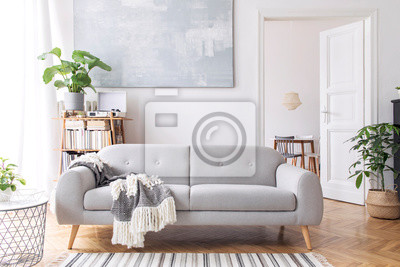 Bild Stylish scandianvian living room with design sofa with elegant blanket, coffee table and bookstand on the white wall. Brown wooden parquet. Concept of minimalistic decor interior with piano. Mock up.