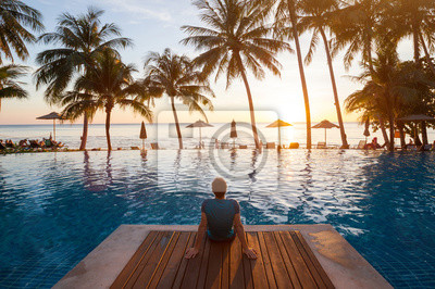 Bild summer holiday getaway in luxury beach hotel, tourist relaxing near luxurious swimming pool at sunset, vacation on tropical island