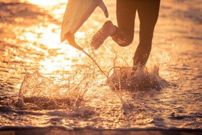 Bild Surfer läuft im Wasser mit seinem Brett