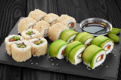 Bild Sushi rollt mit Avocado, Lachs und Sesam auf Schiefer Tablett.