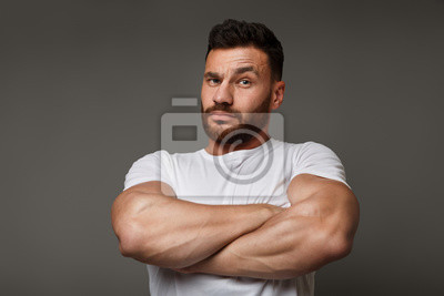 Bild Suspicious young man with crossed big muscular arms