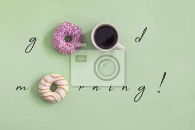 Bild Süßer und bunter Satz Schaumgummiringe mit Tasse Kaffee auf dem grünen Hintergrund. Konzept des guten Morgen Slogans