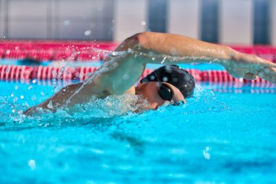 Bild Swimmer man doing crawl swim in swimming pool portrait. Closeup of athlete wearing goggles, swimming cap training in blue water indoors.
