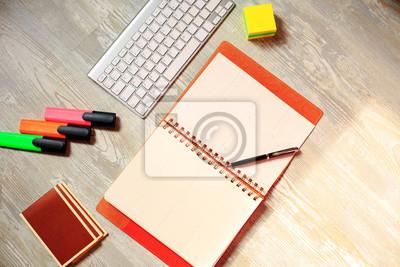Bild Tagebuch (Notizbuch) und farbige Stifte auf hölzernem Hintergrund.