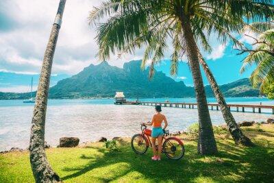 Bild Tahiti travel biking tourist on electric bicycle rental in Bora Bora island , French Polynesia eco-tourism summer vacation adventure fun cyclist girl relaxing at landscape on E-bike biking.