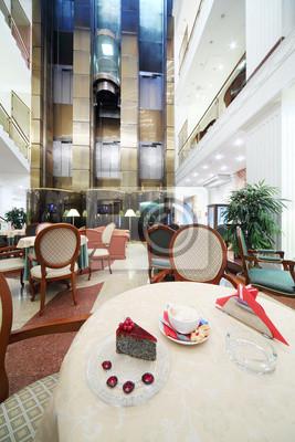 Bild Tasse Kaffee und Stück Kuchen auf dem Tisch in der Halle auf großen Hotel.