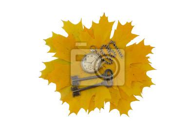 Tasten und alte Taschenuhr auf einem Hintergrund von gelben Blättern. Isolieren