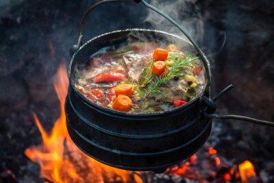 Bild Tasty and spicy hunter's stew on bonfire