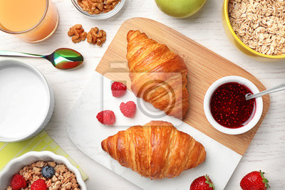 Bild Tasty breakfast with croissants served on white wooden table, flat lay