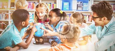 Bild Teacher and kids discussing globe