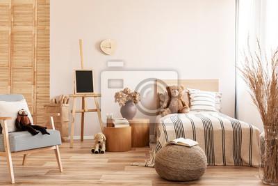 Bild Teddy bear on single wooden bed in natural kid's bedroom
