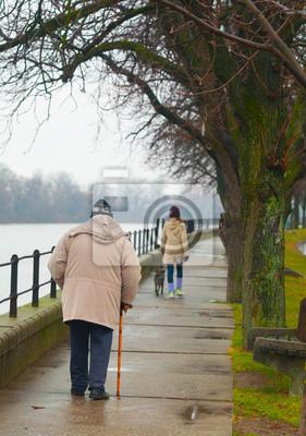 Teenager-Mädchen mit Hund und alter Mann zu Fuß neben dem Fluss