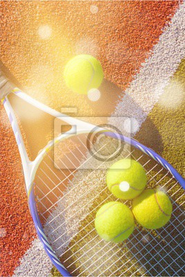 Tennis game. Tennis balls and racket on court background.