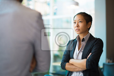 Bild Tense Asian businesswoman looking at male partner with crossed arms. Two colleagues confronting each other in office space. Clashing personalities concept