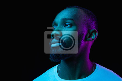 Bild The retro wave or synth wave portrait of a young happy serious african man at studio. High Fashion male model in colorful bright neon lights posing on black background. Art design concept