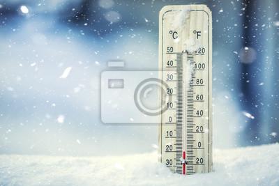 Bild Thermometer auf Schnee zeigt niedrige Temperaturen unter Null. Niedrige Temperaturen in Grad Celsius und Fahrenheit. Kaltes Winterwetter zwanzig unter Null.