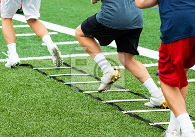Bild Three athletes in cleats doing ladder foot drills on turf field