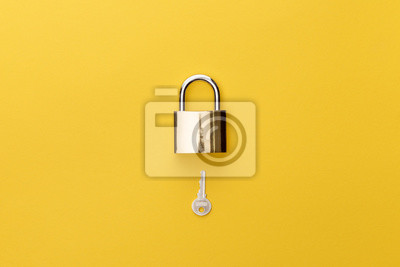 Bild top view of padlock and key on yellow background
