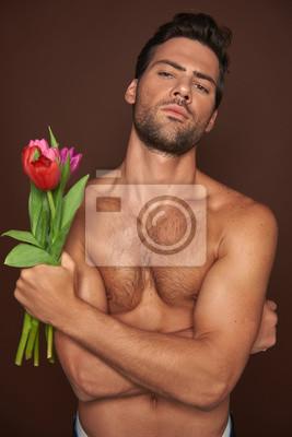 Bild Topless muscular macho man with tulips bunch