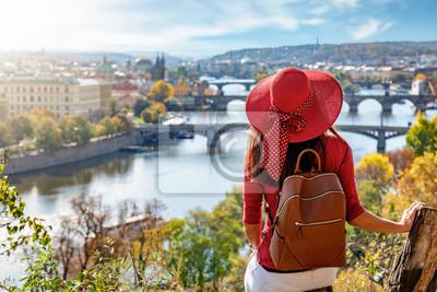 Bild Touristin mit Hut genießt die Aussicht auf die Karlsbrücke und die Altstadt von Prag, Tschechiche Republik, an einem sonnigen Herbsttag